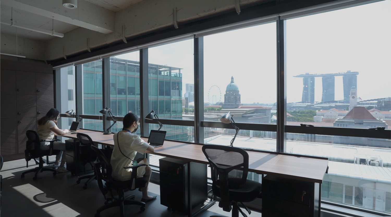 people working in office overlooking Singapore skyline